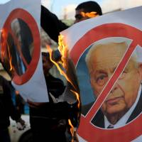 Fired up: Palestinians burn a poster of the former Israel Prime Minister Ariel Sharon in Khan Younis, Gaza Strip, on Saturday. Sharon died the same day, eight years after a debilitating stroke put him into a coma. He was 85. | AP