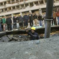 Dangerous place: An Egyptian firefighter looks at a crater following an explosion outside the headquarters of Egypt's police force in downtown Cairo on Friday. Three bombings hit high-profile targets in the capital the same day, one of which was the suicide car bombing at police headquarters in which several people died. It was the first major attack in Cairo as insurgents stepped up a campaign of violence months after the ouster of Islamist President Mohammed Morsi. | AP
