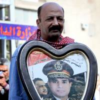Heroes past, present: An Egyptian man carrying a poster with portraits of late leaders Gamal Abdel Nasser (left) and Anwar Sadat (right), alongside current Defense Minister Gen. Abdel-Fattah el-Sissi, stands at the site of a bomb attack in Cairo on Friday. | AFP-JIJI