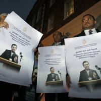 Pressing their case: Demonstrators hold signs with pictures of Al Jazeera journalist Abdullah al-Shami, who with cameraman Mohamed Badr remains in custody in Egypt, at a protest calling for their release outside the Egyptian Embassy in London on Nov. 12. | AP