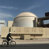Along for the ride?: A worker rides a bicycle in front of the reactor building of the Bushehr nuclear power plant, just outside the southern Iranian city of Bushehr in October 2010. | AP