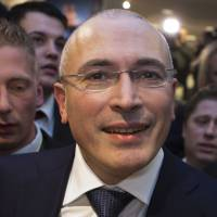 On the move: Former Russian oil tycoon and Kremlin critic Mikhail Khodorkovsky leaves the Wall Museum at Checkpoint Charlie in Berlin after a Dec. 22 news conference. On Sunday Khodorkovsky arrived in Switzerland. | AFP-JIJI