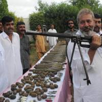 Crime-buster: Senior police investigator Chaudary Aslam holds a machine gun recovered from Pakistani militants with other ammunition in Karachi on May 11, 2012. | AP