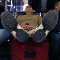Temporarily stranded: A traveler at Boston's Logan International Airport on Monday rests his feet on his luggage as he takes a nap after his flight to Puerto Rico was canceled. | AP