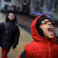 Taste of winter: A boy catches snowflakes on his tongue as his brother follows on their way home from a clinic Thursday in York, Pennsylvania. | AP