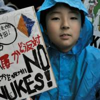 Making a stand: A boy holds a banner denouncing nuclear power during a protest in front of the Prime Minister's Official Residence in Tokyo in July 2012.  | AFP-JIJI