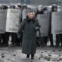 Chip off the old blocked: An elderly woman walks away from police officers blocking a street during unrest between security forces and protesters in central Kiev on Tuesday. | AP