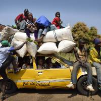 Fares please: Christians crowd a bush taxi 55 km north of Bangui on Sunday as they head to the capital to sell some products on the market. | AFP-JIJI
