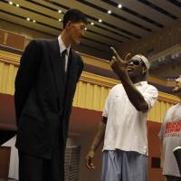 Tall tales: Former NBA player Dennis Rodman meets with ex-North Korean basketball player Ri Myung Hun at a practice session with American and North Korean players in Pyongyang on Tuesday. | AP