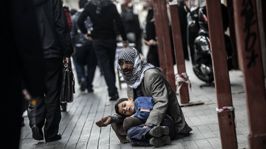 Lost souls: A Syrian man begs for money with a child in Istanbul on Tuesday. | AFP-JIJI
