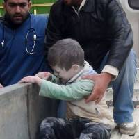 Tiny victim: An injured child is helped following an airstrike by Syrian government forces near a school in Aleppo on Tuesday. | AFP-JIJI