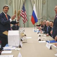 Gourmet goods: U.S. Secretary of State John Kerry holds up two Idaho potatoes as a gift for Russian Foreign Minister Sergey Lavrov at the start of their meeting at the U.S. ambassador's residence in Paris on Monday. | AP