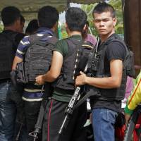 Poll position: Thai soldiers stand in line before voting at a polling station in Pattani, southern Thailand, on Sunday. | AFP-JIJI