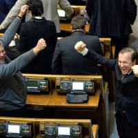 Victory: Members of Ukraine's Regions Party celebrate Wednesday in parliament after a bill was passed granting amnesty to protesters who have been arrested. | AFP-JIJI