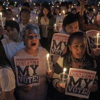Stuck in the middle: Members of Thailand's 'White Shirt' movement hold a candlelight vigil to demand democratic elections and political reforms in Bangkok on Friday. | AP