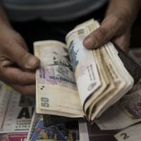 Cashing in: A newsstand owner counts Argentine pesos in Buenos Aires on Friday after the country lifted restrictions in place since 2011 that limited the purchase of foreign currency. | AFP-JIJI
