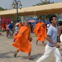 Decamped: Cambodian Buddhist monks and protesters run as security personnel armed with shields and batons flood into the opposition's rally camp at Phnom Penh's Democracy Park on Saturday. | AFP-JIJI