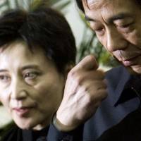 Pouncing on 'tigers': Gu Kailai (left), wife of China's then-commerce minister, Bo Xilai (right), attends a memorial ceremony for Bo's father at a military hospital in Beijing in January 2007. Bo was one of the biggest names in the Communist Party to be caught in the net of Chinese President Xi Jinping's anti-corruption crackdown. | AP