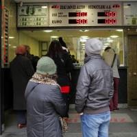 Lagging lira: Pedestrians stop and look at foreign currency exchange rates on an electronic board in Istanbul, Turkey, on Monday. The lira appreciated the most this month amid speculation the Central Bank of Turkey will raise interest rates at a surprise policy meeting tomorrow. | BLOOMBERG