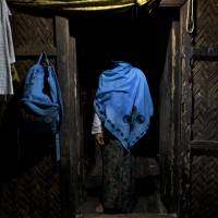 Living in fear: A woman who claims she was raped by Myanmar security forces stands in her home in northern Myanmar on Sept. 15, 2013. The use of sexual violence against civilians in Myanmar remains widespread and systematic, said Tin Tin Nyo, general secretary of the Women's League of Burma. | AP