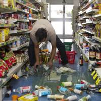 Shake down: A shop owner lifts stock from the floor in the small Wairarapa town of Eketahuna on Monday, after a strong 6.3-magnitude earthquake rattled New Zealand, halting train services and knocking merchandise off shelves. There were no immediate reports of major damage or injuries. | AFP-JIJI