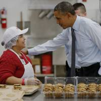 Gingersnap decisions: President Barack Obama greets an employee in the bakery at a Costco store in Lanham, Maryland, on Wednesday morning before giving a speech about raising the minimum wage. | AP