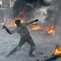 Fired up:  A protester throws a Molotov cocktail towards riot police during a clash in central Kiev on Saturday. Ukraine's Interior Ministry has accused protesters of capturing two of its officers as violent clashes have resumed in the capital and anti-government riots spread across Ukraine. | AP