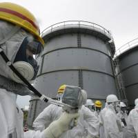 Suit up: An Tokyo Electric Power Co. official measures radiation levels where radioactive water leaked from a storage tank in August, at the Fukushima No. 1 nuclear power plant in Okuma, Fukushima Prefecture on Nov. 7. | AP