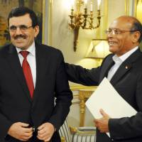 Out with a smile: Tunisian Prime Minister Ali Larayedh (left) smiles after presenting his resignation to President Moncef Marzouki on Thursday in favor of a caretaker government that will supervise new elections later this year. | AP