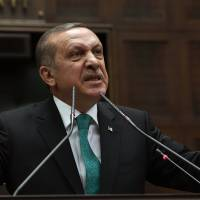 Opportunity knocks?: Turkey's Prime Minister Recep Tayyip Erdogan addresses his supporters during parliament in Ankara on Jan. 14, 2014.  Turkish anti-terrorism police carried out raids in six cities on Tuesday, detaining at least five people with alleged links to al-Qaida, including an employee of a prominent Islamic charity group that provides aid to Syria, media reports and officials said. | AP