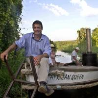 Sitting pretty: Cam McLeay, owner of the African Queen, sits on his boat on the shores of the River Nile in Uganda in December 2013. Sixty years after Humphrey Bogart steered her through crocodile infested waters, the African Queen is back plying its old route. | AFP