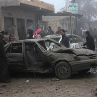 Charred: Civilians inspect the aftermath of a massive bomb attack in Balad Ruz, northeast of Baghdad, on Friday. Officials in Iraq say scores were killed when a pickup truck laden with explosives blew up on a busy commercial street there Thursday.   AP
