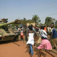 No peace: Demonstrators march past a French Sagay tank of the Sangaris force on their way to Mpoko airport Friday in Bangui, as the Central African Republic's president, Michel Djotodia, awaited a verdict on his future amid sectarian violence ripping his country apart. | AFP-JIJI