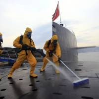 Running clean: Chinese sailors in protective gear clean and disinfect a nuclear submarine during a drill at Qingdao submarine base in Shandong province on July 17, 2013. | AP