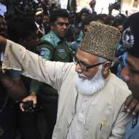 Sentenced to die: Matiur Rahman Nizami, head of Bangladesh's main Islamist opposition party, enters a prison van outside a court in Chittagong on Thursday after he was sentenced to death on charges of smuggling weapons to a rebel group in neighboring India. | AP