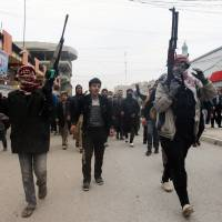 On the war path: Mourners and Sunni gunmen chant slogans against Iraq's Shiite-led government during the funeral of a man killed when clashes erupted Friday between al-Qaida gunmen and Iraqi soldiers, his family said in Fallujah on Saturday. | AP