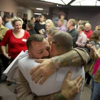 Chris Serrano (left) and Clifton Webb embrace after being married Dec. 20 as people wait in line to get licenses outside of the marriage division of the Salt Lake County Clerk's Office in Salt Lake City. | AP