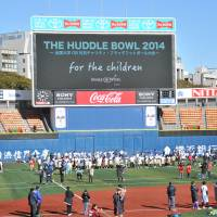 All together: Former or active tackle football players participated in the Huddle Bowl, a charity flag football tournament, on Sunday. | HIROSHI IKEZAWA