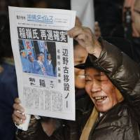 Hot off the press: A supporter of Mayor Susumu Inamine raises a special edition of a local newspaper predicting his re-election Sunday in Nago, Okinawa Prefecture. | KYODO