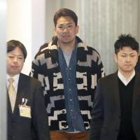 Calling card: Pitcher Masahiro Tanaka arrives at Narita airport on Saturday after a trip to the United States to meet major league teams.   KYODO