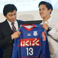 New horizons: Indonesian forward Irfan Bachdim (right) holds a Ventforet Kofu shirt on Monday after signing with the J. League first-division club. | KYODO