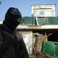 Tough day: An Afghan policeman stands guard next to the damaged entrance of a Lebanese restaurant that was attacked in Kabul on Saturday, killing at least 21 people, including 13 foreigners. | AFP-JIJI