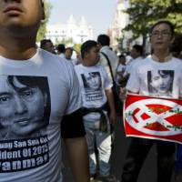 Presidential push: Supporters of Myanmar opposition leader Aung San Suu Kyi, wearing T-shirts bearing her portrait, take part in a protest march in Yangon on Friday to push for her to become president. Suu Kyi's party has started holding meetings with the public to assess their views on amending or redrafting the country's army-dictated 2008 constitution, which disqualifies her from becoming president. | AP