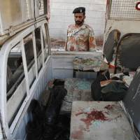 Perpetual carnage: A Pakistani security officer looks at a vehicle targeted by militants in Karachi. Police said several members of the country's security forces have been killed in separate attacks in the southern city.   AP