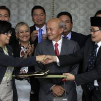 Peace in their time?: Miriam Ferrer (front left), chairwoman of the Philippine Government Peace Panel, and Mohagher Iqbal (front right), chief negotiator for the Moro National Liberation Front, exchange signed documents in Kuala Lumpur on Saturday after striking a deal to end four decades of fighting. | AP