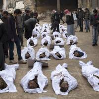 Slain kin: Men search for their relatives among the bodies of Syrian civilians executed and dumped in the Quweiq River, in the grounds of the courtyard of the Yarmouk School, in the Bustan al-Qasr district of Aleppo last Jan. 30. | AFP-JIJI