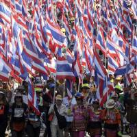 Anti-government protesters with national flags gather for a rally Tuesday in Bangkok.   AP