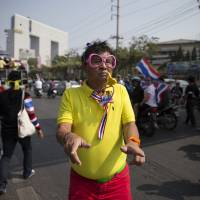 Undaunted: An anti-government protestor dances in the street during a march Sunday in Bangkok. Two explosions shook an anti-government demonstration site in Thailand's capital on Sunday, wounding at least 28 people. | AP