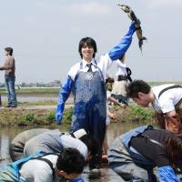 Kohey Takashima, Oisix Inc. president and a Young Global Leader alumnus of the World Economic Forum, holds up a renkon (lotus root) during a company event in which employees experience harvesting vegetables with an Oisix contracted farmer in Chiba Prefecture in April 2007. | OISIX INC.