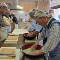 A soba-making class at a community center. Participants knead buckwheat dough by hand, roll it out and cut it into noodles. | MICHIKO EBINA